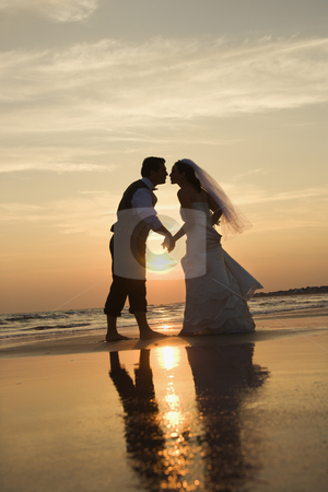 Bride and groom kissing. stock photo, Caucasian prime adult male groom and female bride holding hands and kissing barefoot on beach at sunset. by Iofoto Images