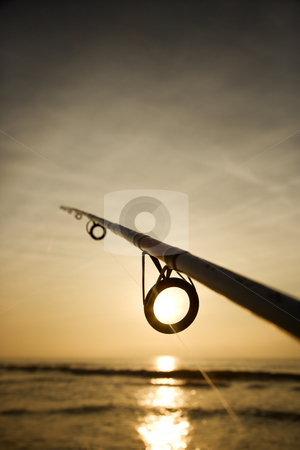 Fishing pole with ocean. stock photo, Fishing pole against ocean at sunset. by Iofoto Images