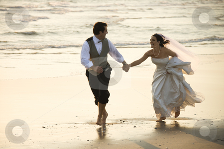 Bride and groom on beach. stock photo, Caucasian prime adult male groom and female bride running barefoot on beach. by Iofoto Images