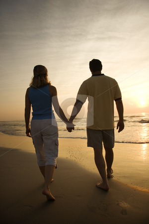 Couple on beach at sunset. stock photo, Caucasian mid-adult couple walking holding hands on beach at sunset. by Iofoto Images