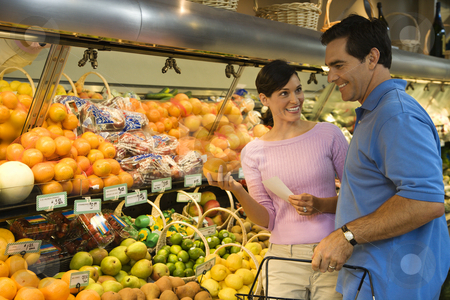 Couple grocery shopping. stock photo, Caucasian mid-adult couple grocery shopping for fruit looking at each other smiling. by Iofoto Images