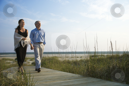 Couple holding hands. stock photo, Caucasian mid-adult couple holding hands and walking down walkway at beach. by Iofoto Images