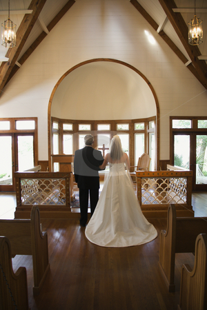 Bride and groom. stock photo, Portrait of bride and groom at alter of a church. by Iofoto Images
