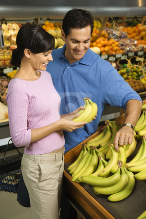 Couple grocery shopping. stock photo, Caucasian mid-adult couple grocery shopping for bananas. by Iofoto Images