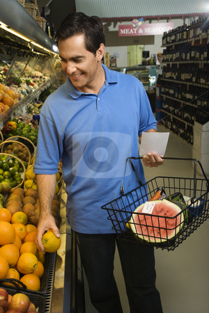 Man grocery shopping. stock photo, Caucasian mid-adult male grocery shopping for fruit. by Iofoto Images