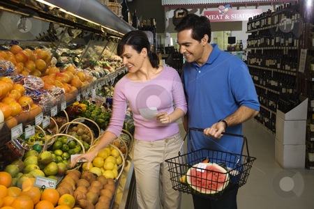 Couple grocery shopping. stock photo, Caucasian mid-adult couple grocery shopping for fruit. by Iofoto Images