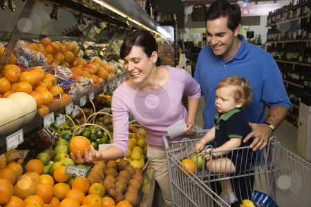 Family grocery shopping. stock photo, Caucasian mid-adult parents grocery shopping for fruit with male toddler. by Iofoto Images