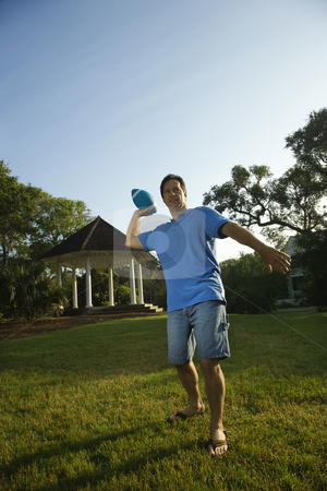 Man throwing football. stock photo, Caucasian mid-adult man throwing football. by Iofoto Images