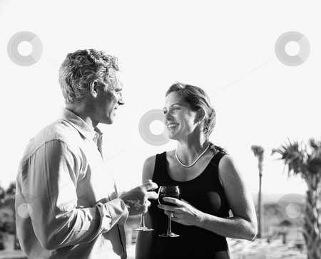 Caucasian couple holding wine glasses. stock photo, Black and white image of mid-adult Caucasian couple holding wine glasses and smiling at each other. by Iofoto Images