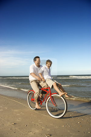 Dad riding red bicycle with son on handlebars.  stock photo, Caucasian father on bicycle with pre-teen boy riding on handlebars. by Iofoto Images