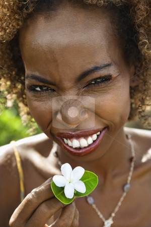 Woman holding jasmine flower. stock photo, Portrait of mid-adult African American female squinting and holding jasmine flower. by Iofoto Images