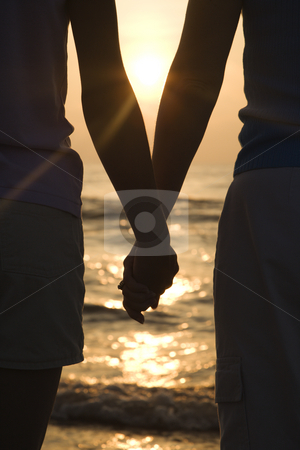 Mom and daughter holding hands. stock photo, Caucasian mid-adult mother and teenage daughter standing on beach at sunset holding hands. by Iofoto Images
