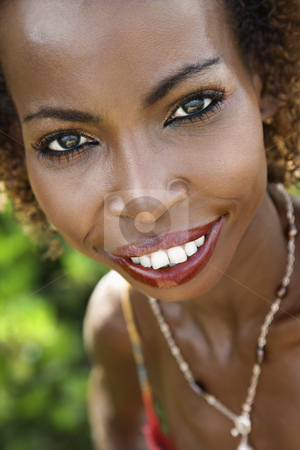Portrait of smiling woman. stock photo, Portrait of mid-adult African American female smiling and making eye contact. by Iofoto Images
