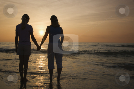 Mom and daughter at sunrise. stock photo, Caucasian mid-adult mother teenage and daughter standing on beach at sunset holding hands. by Iofoto Images