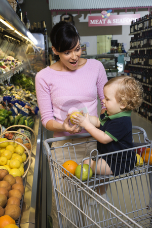 Mother grocery shopping with toddler. stock photo, Caucasian mid-adult woman grocery shopping for fruit with young male toddler. by Iofoto Images