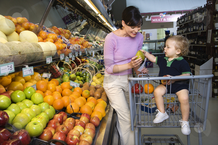 Mother grocery shopping. stock photo, Caucasian mid-adult woman grocery shopping for fruit with young male toddler. by Iofoto Images