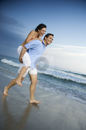 Couple on beach. stock photo, Caucasian mid-adult male carrying female piggyback style on beach. by Iofoto Images