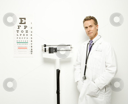 Doctor with scale. stock photo, Mid-adult Caucasian male doctor standing next to scale with eye chart on wall. by Iofoto Images