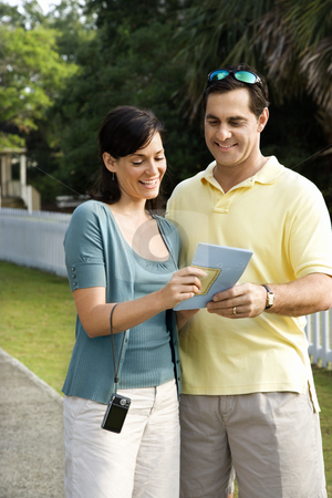 Couple holding map. stock photo, Mid-adult Caucasian couple holding map and smiling. by Iofoto Images