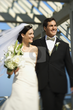 Bride and groom walking. stock photo, Caucasian mid-adult bride and groom walking together smiling. by Iofoto Images