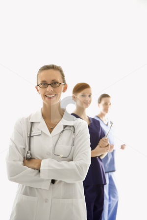 Doctor and nurse. stock photo, Portrait of smiling Caucasian medical healthcare workers in uniforms standing against white background. by Iofoto Images