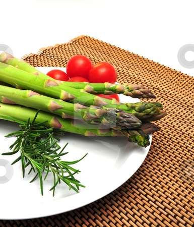 Asparagus With Cherry Tomatos stock photo, Asparagus and cherry tomatos on a white saucer and wooden place mat by Lynn Bendickson