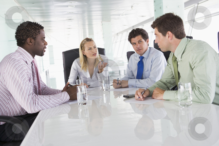 Four businesspeople in a boardroom talking stock photo,  by Monkey Business Images