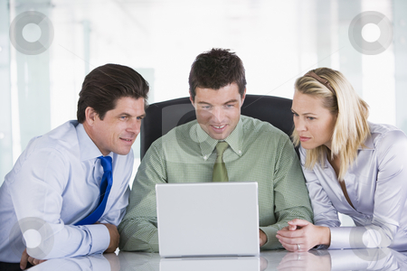 Three businesspeople in a boardroom looking at laptop stock photo,  by Monkey Business Images