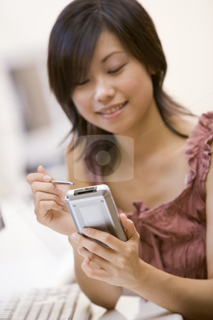 Woman in computer room using personal digital assistant smiling stock photo,  by Monkey Business Images