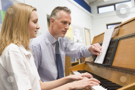 Teacher with schoolgirl playing piano in music class stock photo,  by Monkey Business Images