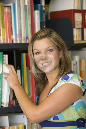 Female college student reaching for a library book