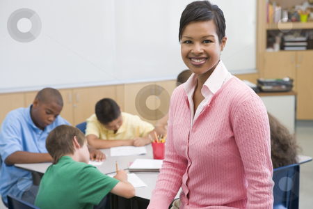 Elementary school teacher stock photo, Elementary school teacher with pupils in background by Monkey Business Images