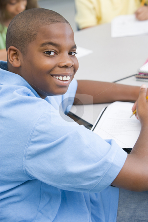 Elementary school pupil stock photo, Elementary school pupil working at desk by Monkey Business Images