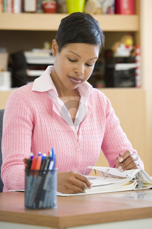 Elementary school teacher stock photo, Elementary school teacher writing reports by Monkey Business Images
