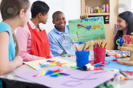 Elementary school art class stock photo, Elementary school art class with pupil discussing picture by Monkey Business Images