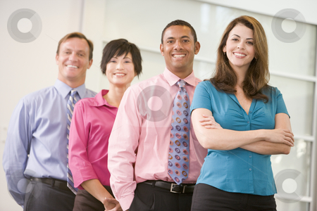Business team standing indoors smiling stock photo,  by Monkey Business Images