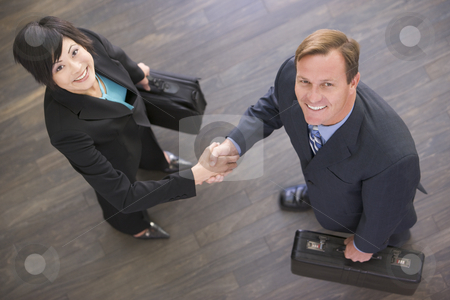 Two businesspeople indoors shaking hands smiling