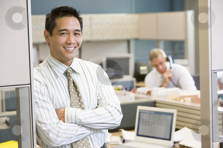 Businessman standing in cubicle smiling stock photo,  by Monkey Business Images