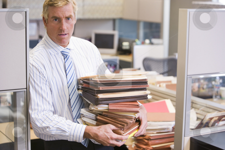 Businessman standing in cubicle holding stacks of files stock photo,  by Monkey Business Images