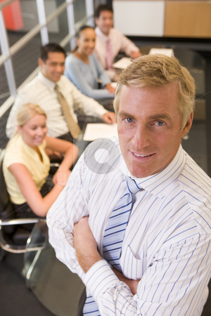 Businessman with four businesspeople at boardroom table in backg stock photo,  by Monkey Business Images