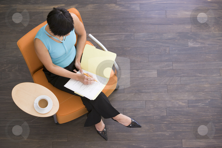Businesswoman sitting indoors with coffee and folder stock photo,  by Monkey Business Images