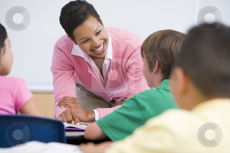 Elementary school teacher with pupils stock photo, Elementary school teacher with pupils in classroom by Monkey Business Images