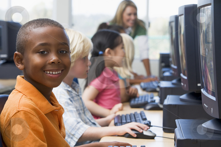 Kindergarten children learning how to use computers. stock photo,  by Monkey Business Images