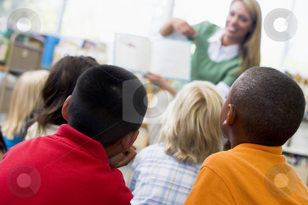 Kindergarten teacher reading to children in library stock photo,  by Monkey Business Images