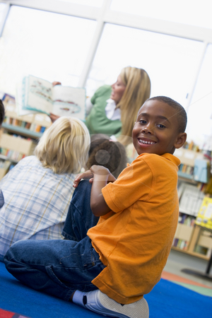 Kindergarten teacher reading to children in library, boy looking stock photo,  by Monkey Business Images