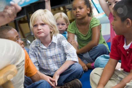 Kindergarten children listening to a story stock photo,  by Monkey Business Images