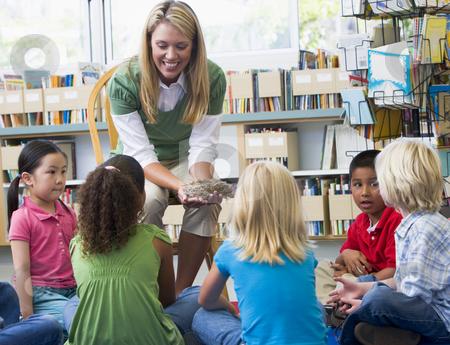 Kindergarten teacher and children looking at bird's nest in libr stock photo,  by Monkey Business Images
