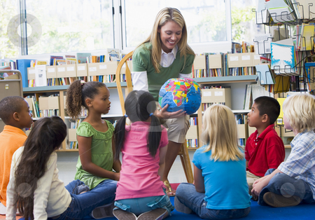 Kindergarten teacher and children looking at globe in library stock photo,  by Monkey Business Images