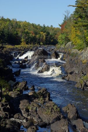 Rocky river rapids stock photo, The rocky river rapids of the St. Louis River reflect a brilliant blue sky on Minnesota fall morning.  The St. Louis River with its slate rock is a prominent feature of Jay Cooke State Park and the river is the primary tributory emptying into Lake Superior. by Dennis Thomsen