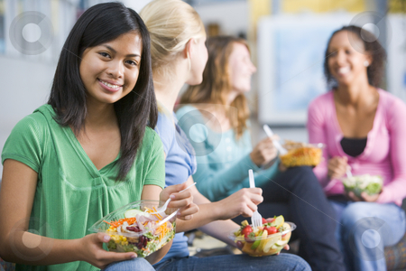 Teenage girls enjoying healthy lunches together stock photo,  by Monkey Business Images